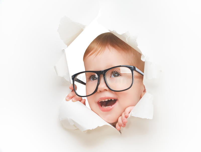 Funny child baby girl with glasses peeping through hole in an empty white paper stock image