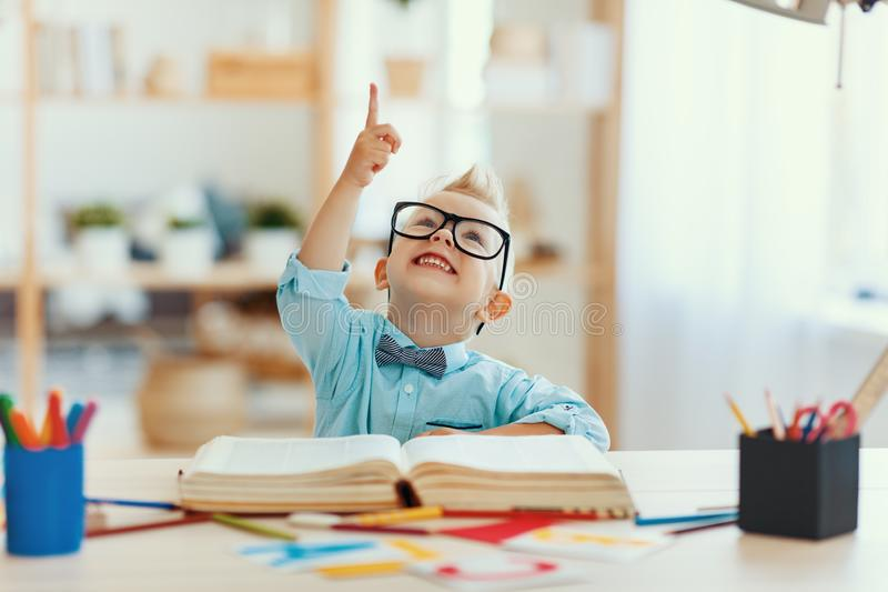 Funny child  boy  doing homework writing and reading at home stock image