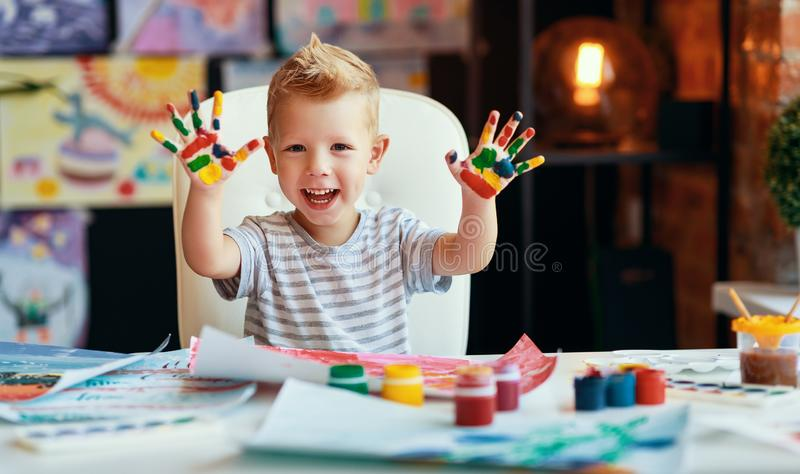 Funny child boy draws laughing shows hands dirty with paint stock image