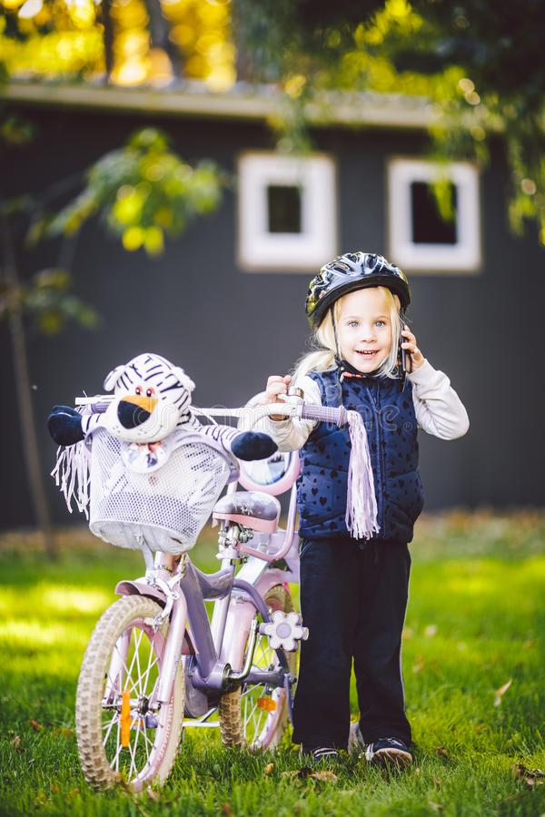 Funny child Caucasian girl blonde in a bicycle helmet near a purple bike with a basket in outside the park on a green royalty free stock photo
