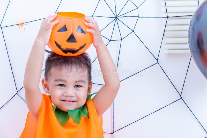 Funny child in costume Halloween he holding orange pumpkin Jack on head stock photography