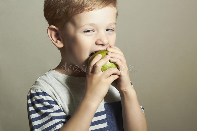 Funny Child eating apple.Little Boy with green apple. Health food. Fruits. Funny Child eating apple.Little Handsome Boy with green apple. Health food. Fruits royalty free stock photos