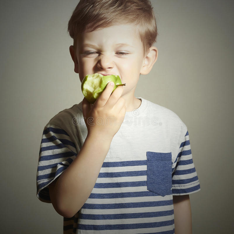 Funny Child eating apple.Little Boy. Health food. Fruits.Vitamin C. Close-up portrait of Funny Child eating apple.Little Boy. Health food. Fruits.Vitamin C stock photo