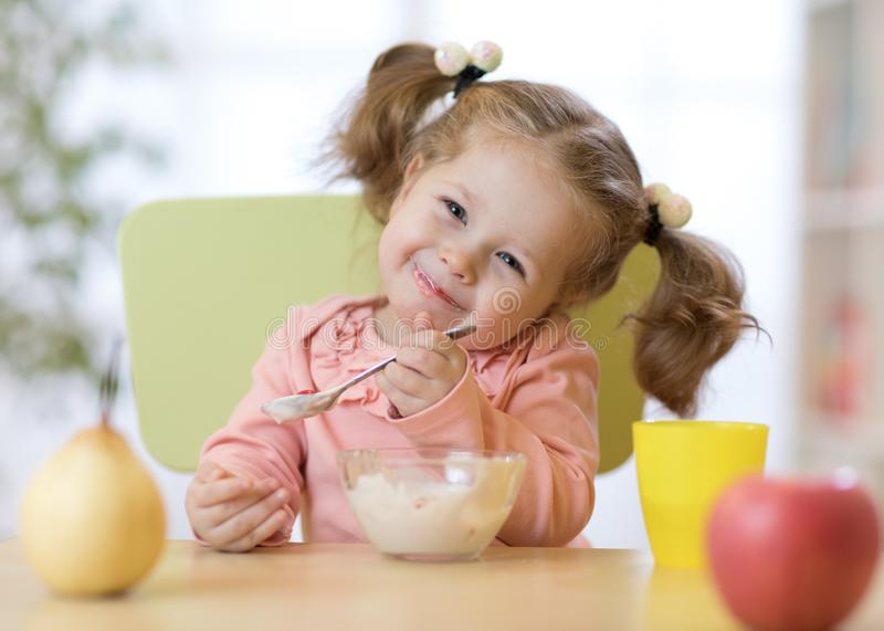 Funny child eating healthy food with a spoon at home royalty free stock photos