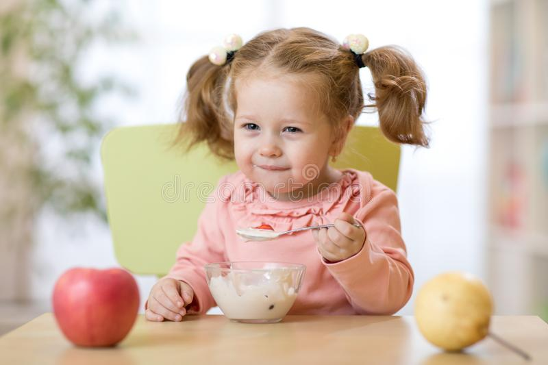 Funny child eating healthy food with a spoon at home stock photography