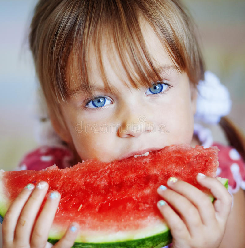 Funny child eating watermelon stock photo