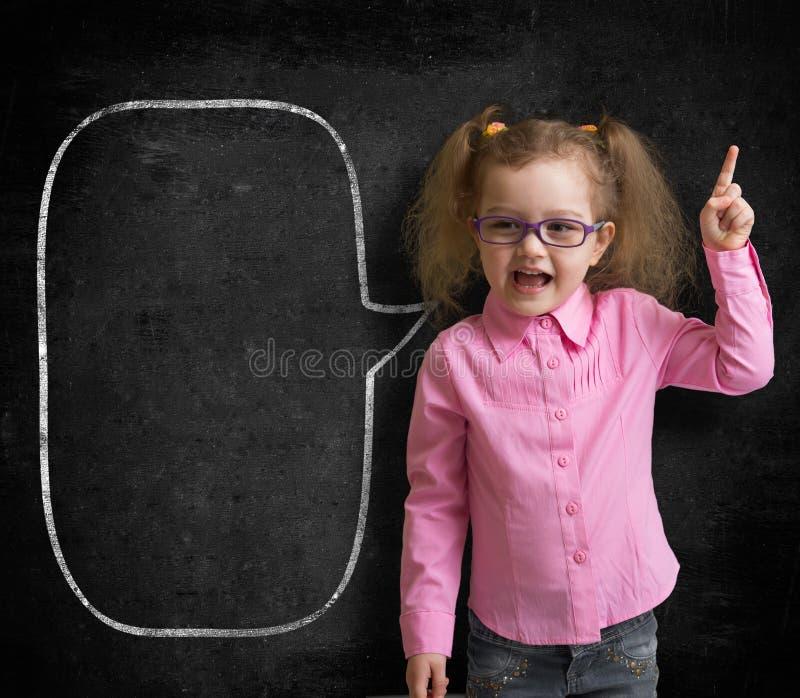 Funny child in eyeglasses standing near school chalkboard royalty free stock photography