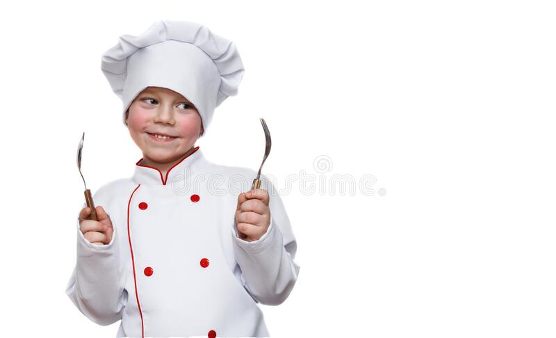 A funny child in the form of a chef with a cap, smiles amusingly, holds a fork and a spoon, looks into an empty seat. Restaurant royalty free stock photography