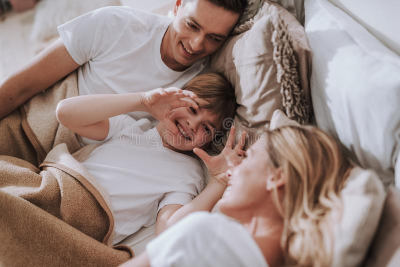 Funny child gesturing while lying in bed between his parents royalty free stock photo