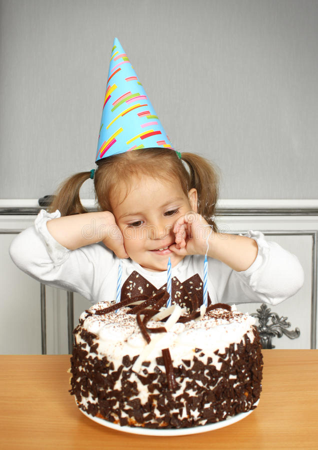 Funny child girl with birthday hat and cake. Portrait of funny little girl with birthday hat and cake stock images