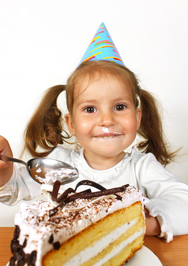 Funny child girl with birthday hat eating cake. Portrait of smeared little girl with birthday hat eating cake stock photo
