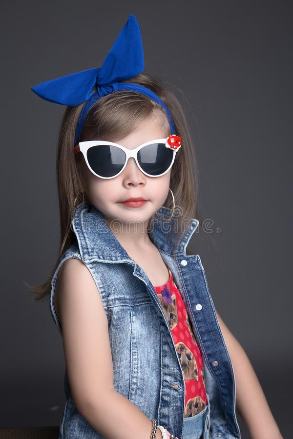 Funny child girl in bow and sunglasses royalty free stock images