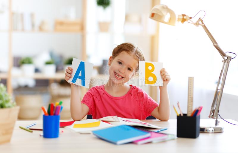 Funny child  girl  doing homework writing and reading at home royalty free stock photo