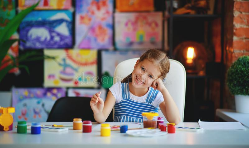 Funny child girl draws laughing shows hands dirty with paint stock photography