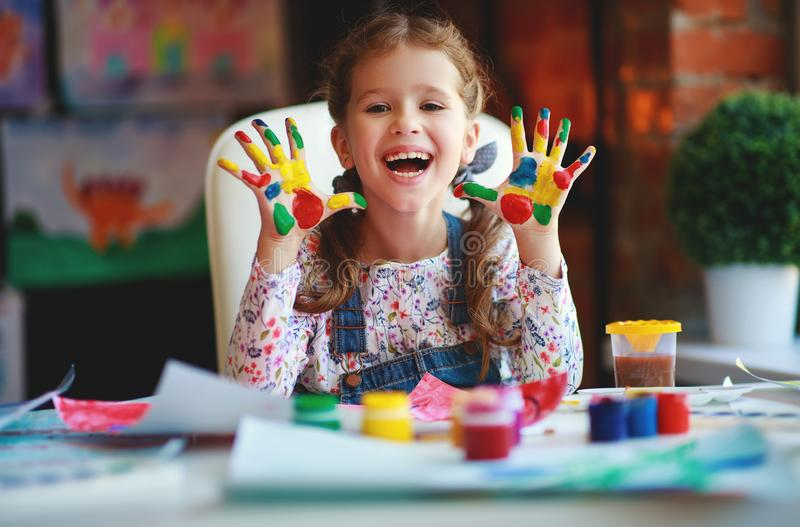 Funny child girl draws laughing shows hands dirty with paint. Happy funny child girl draws laughing shows hands dirty with paint royalty free stock images