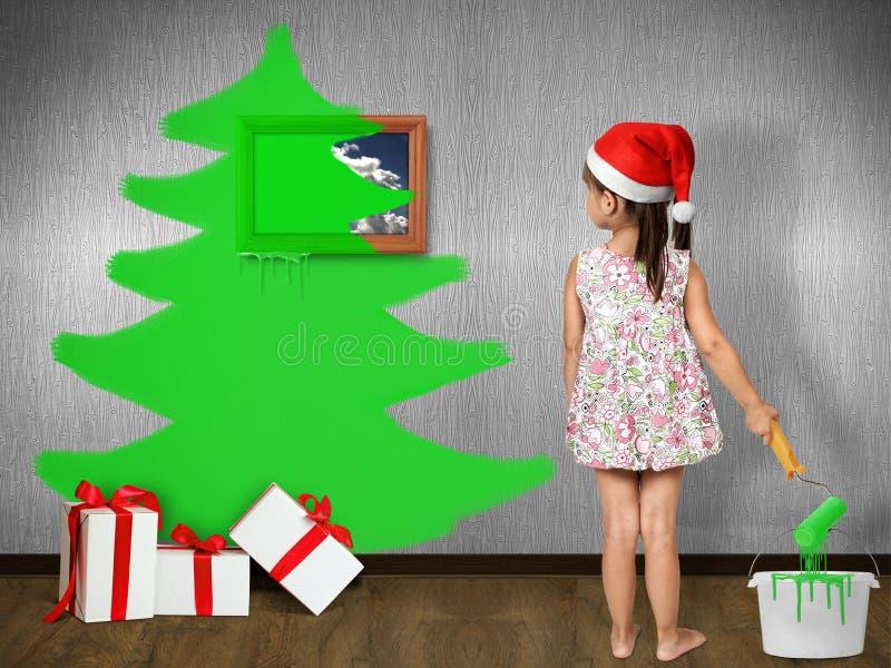 Funny child girl dressed Santa hat, draws Christmas tree on wall royalty free stock photos