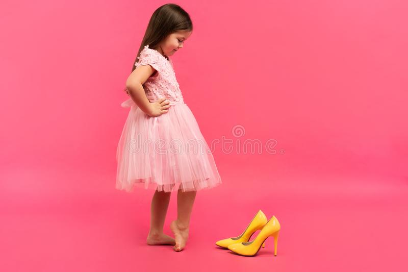 Funny child girl fashionista in dress going to put on big mother`s yellow shoes on colored background. Funny child girl fashionista in dress going to put on big stock photography