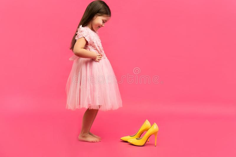Funny child girl fashionista in dress going to put on big mother`s yellow shoes on colored background. Funny child girl fashionista in dress going to put on big stock photo