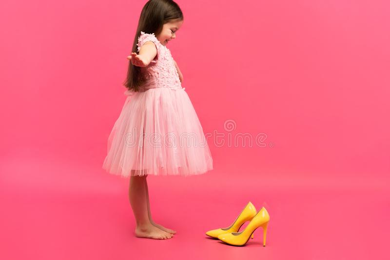 Funny child girl fashionista in dress going to put on big mother`s yellow shoes on colored background. Funny child girl fashionista in dress going to put on big royalty free stock photo
