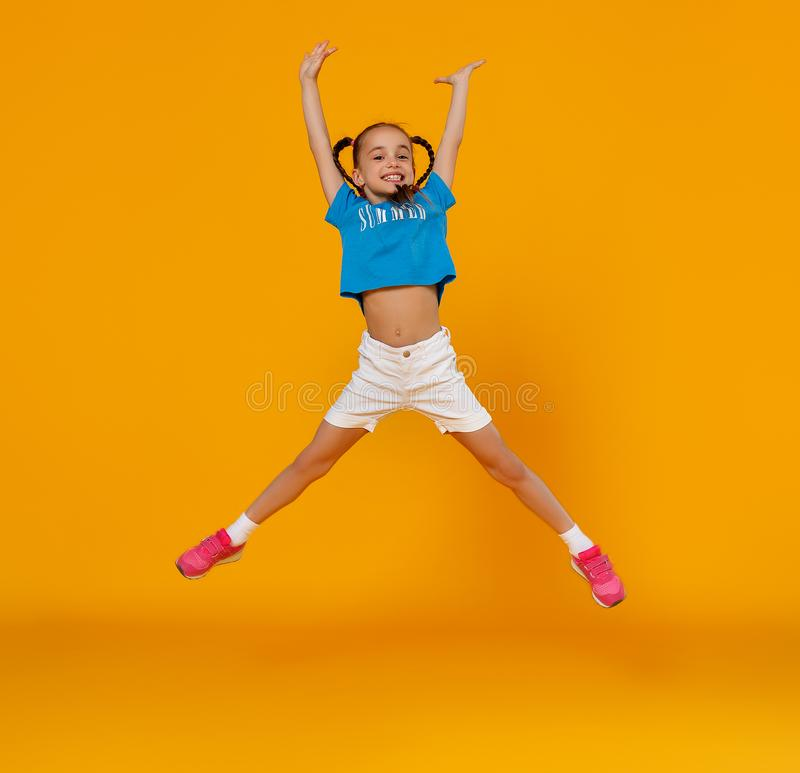 Funny child girl jumping on colored yellow background stock photo