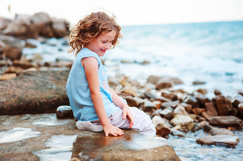 Funny child girl playing with water splash on the beach. Traveling on summer vacation. stock images