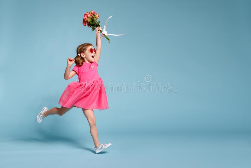 Funny child girl runs and jumps with bouquet of flowers on color stock photos