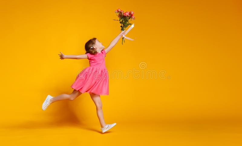 Funny child girl runs and jumps with bouquet of flowers on color royalty free stock photo