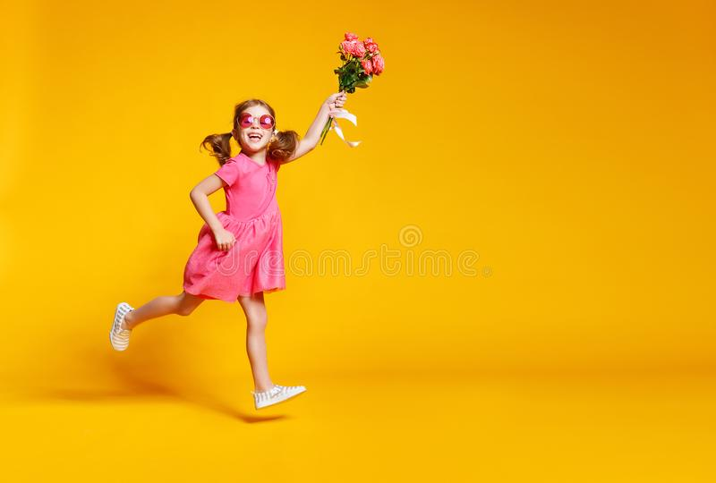 Funny child girl runs and jumps with bouquet of flowers on color royalty free stock images