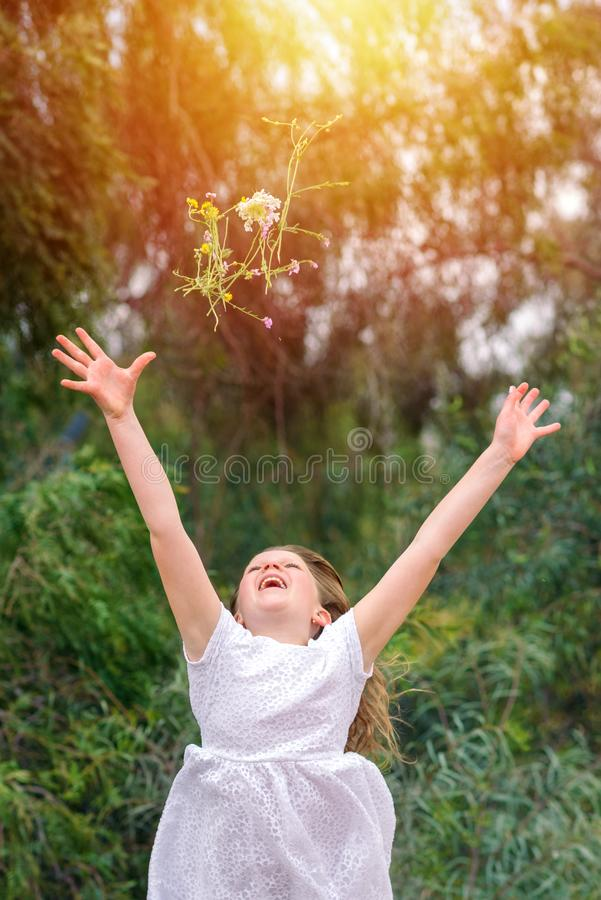 Funny child girl runs, jumps and throws a bouquet of flowers on nature outdoor background. royalty free stock photography