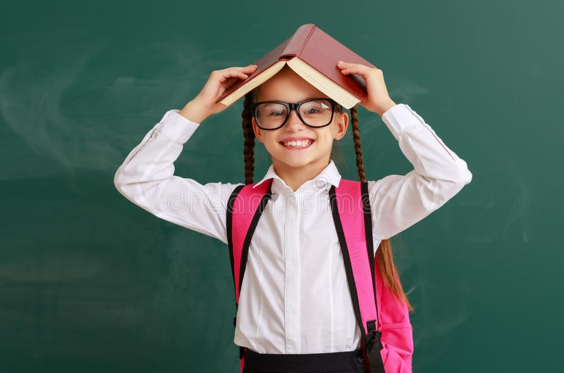 Funny child   girl student with book about school blackboard stock images