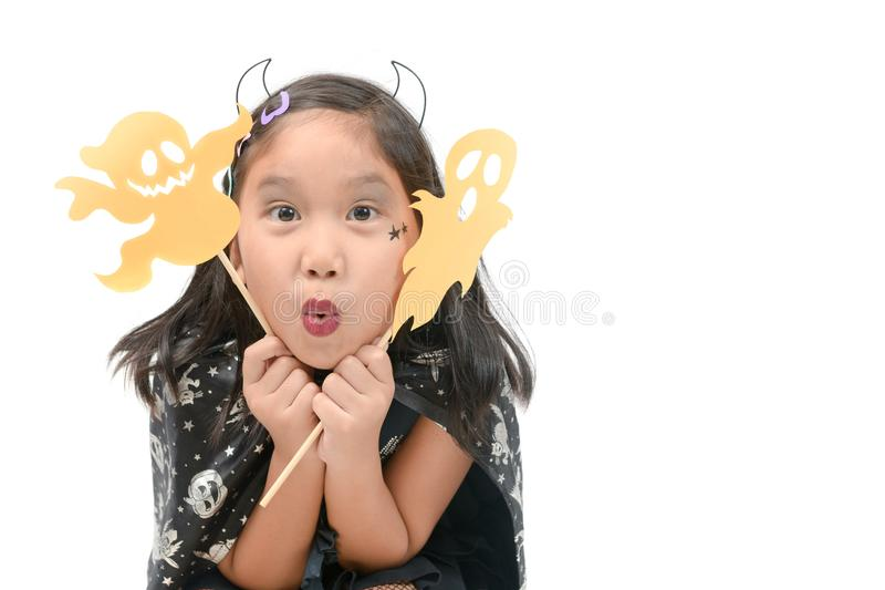 Funny child girl in witch costume for Halloween. Playing paper ghost isolated on white background royalty free stock photography