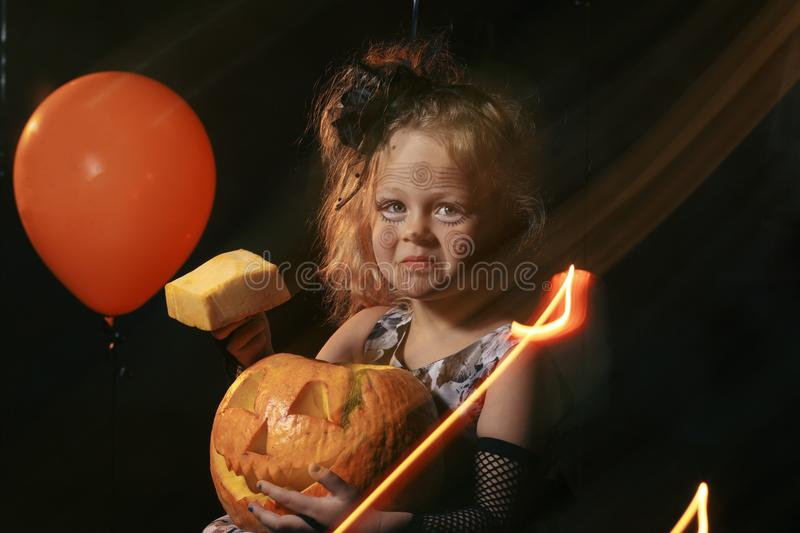 Funny child girl in witch costume for Halloween with pumpkin Jack and orange balloon on a dark background royalty free stock photography