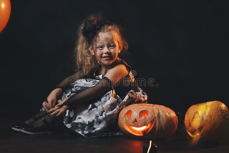 Funny child girl in witch costume for Halloween with pumpkin Jack and orange balloon on a dark wooden background stock images