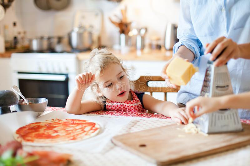 Funny child gourmet is eating and tasting cheese. Family are cooking pizza and preparing homemade italian food stock photos