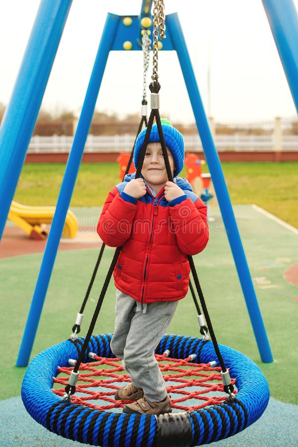 Funny child having fun with modern swing. Little boy playing on outdoor playground. Happy kid swinging on cold autumn day. Active royalty free stock photography