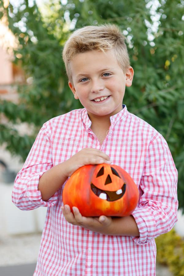 Funny child holding a big pumpkin stock photos