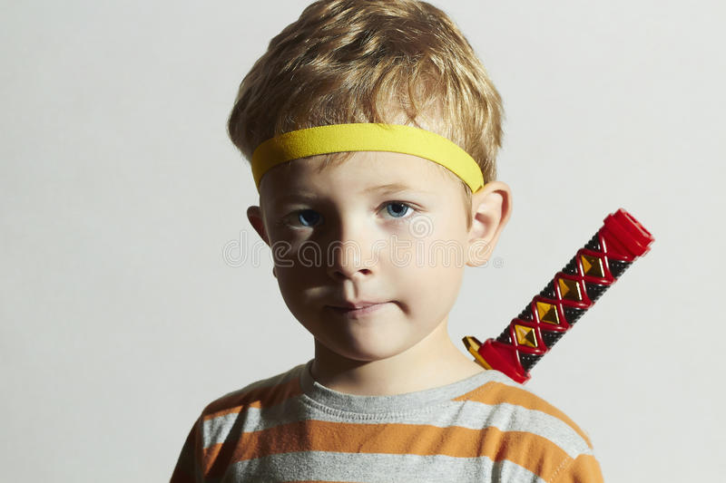 Funny child play ninja.Little Boy with ninja sword.Masquerade.Unusual. Portrait of funny child play ninja.Little Boy with ninja sword.Masquerade.Unusual royalty free stock image
