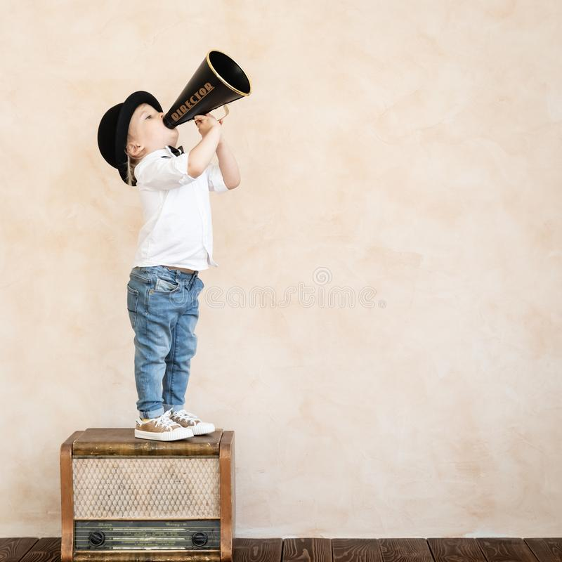 Funny child playing with black retro megaphone stock image