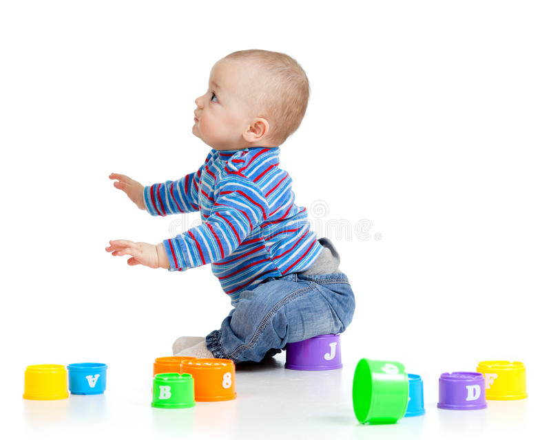 Funny child playing with toys. Funny little child is playing with toys, over white royalty free stock photo