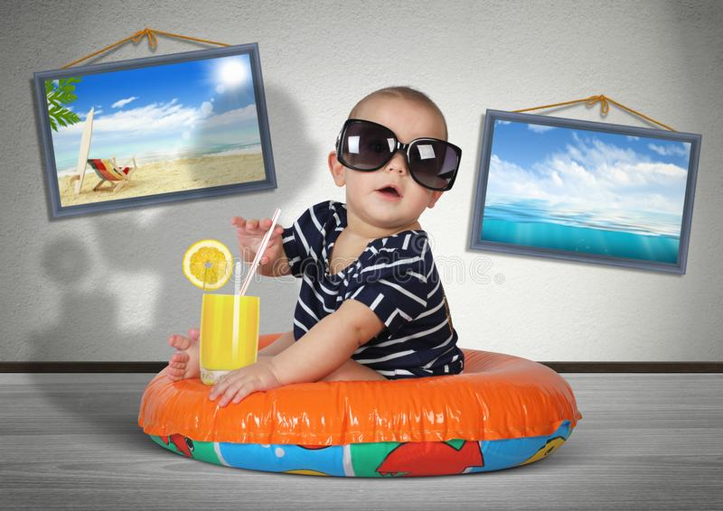 Funny child rest on swimming ring at home, as on the beach. Vacation creative concept. Funny child rest on swimming ring at home, as on the beach. Vacation royalty free stock image