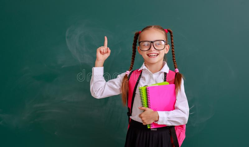 Funny child   schoolgirl girl student with book about school blackboard royalty free stock photography