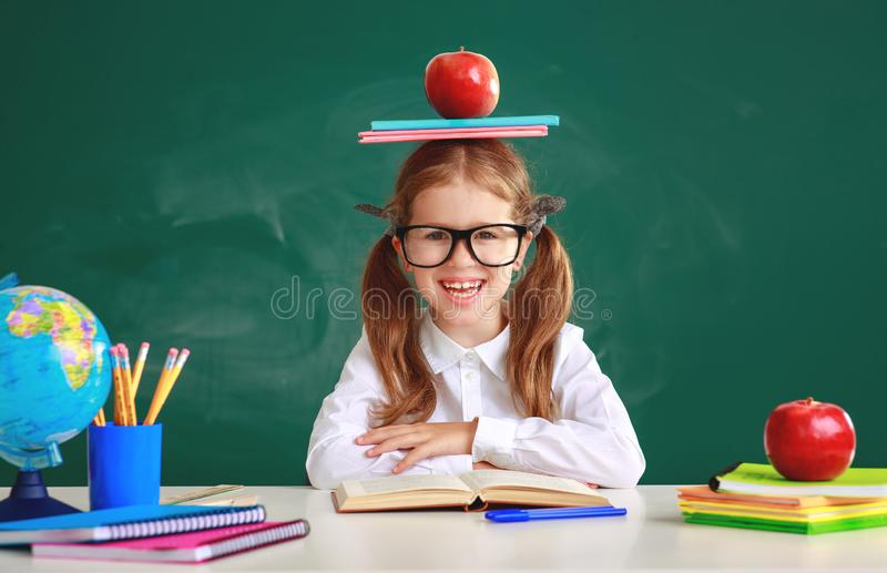 Funny child   schoolgirl  girl student about school blackboard. Funny happy child   schoolgirl  girl student about school blackboard royalty free stock image