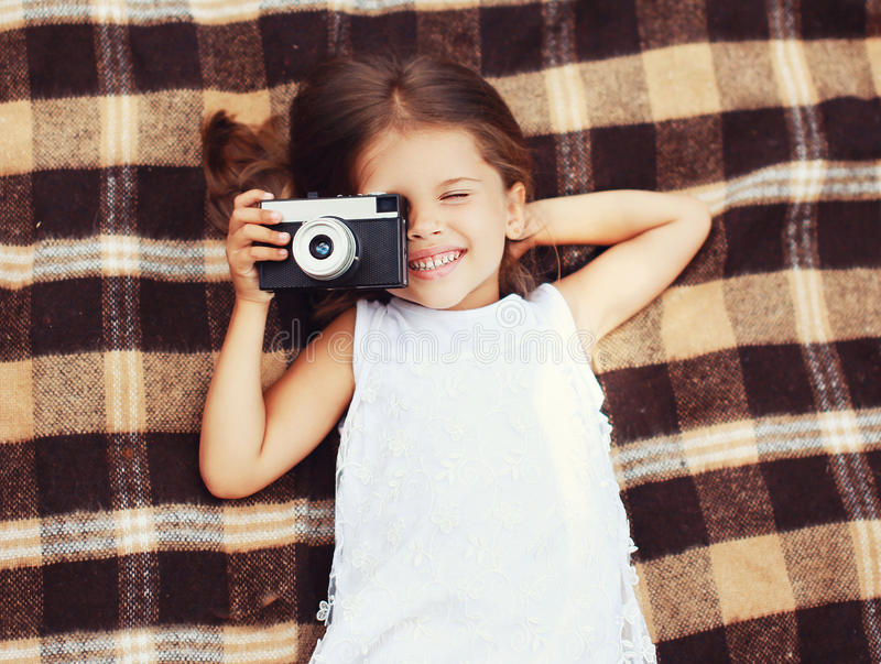 Funny child shooting vintage old retro camera and having fun stock photos