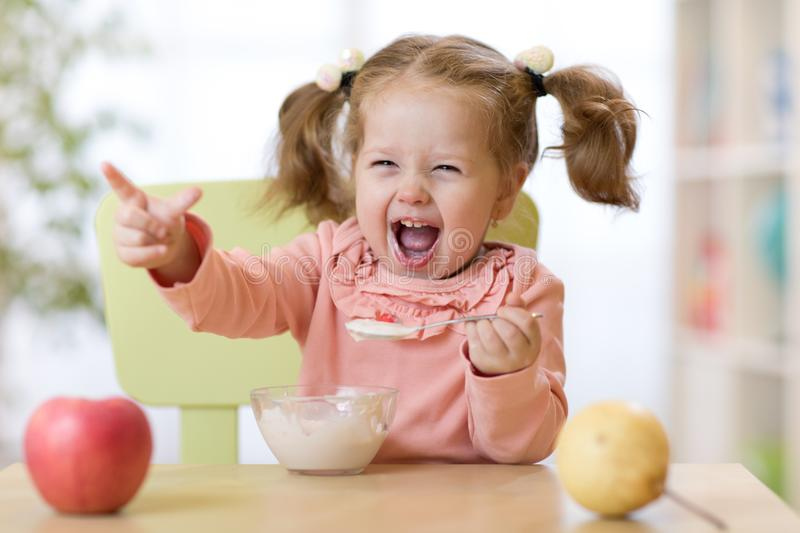 Funny child eating healthy food with a spoon at home stock photo