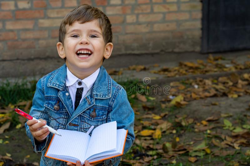 Funny child writing in notebook using pencil and smiling. Two or three years old kid standing on grass. Space for advertising text royalty free stock photos