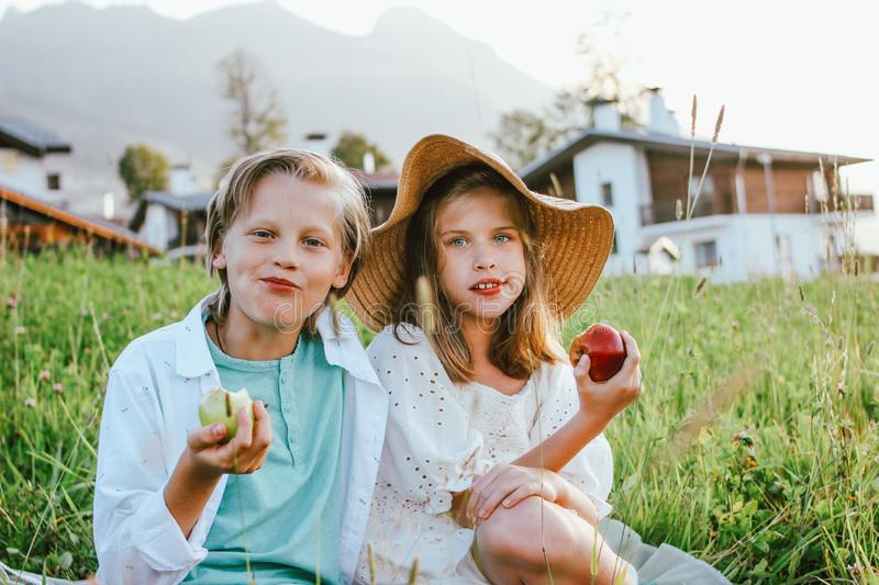 Funny children with apples brother and sister friends sitting in grass, rural scene royalty free stock photos