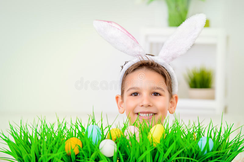 Funny children bunny. Easter holidays. Funny happy boy wearing bunny ears celebrating Easter at home stock image