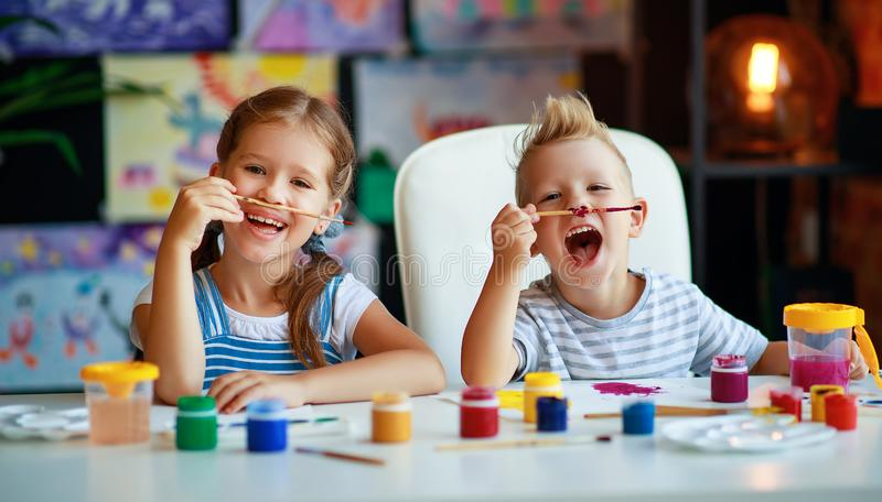 Funny children girl  and boy draws laughing   with paint stock photo