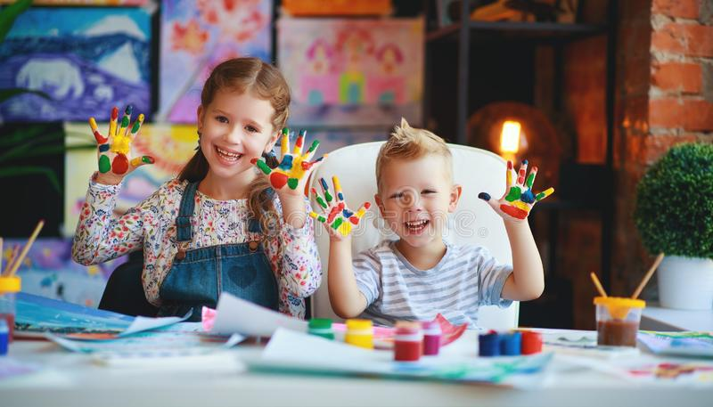 Funny children girl  and boy draws laughing shows hands dirty with paint. Happy funny children girl  and boy draws laughing shows hands dirty with paint stock photo