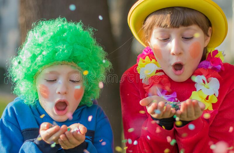 Children girls celebrate carnival smiling and having fun with  colorful confetti stock photos